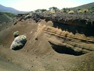 Erosion exposing the layers and layers of lava, ashes, and dirt.